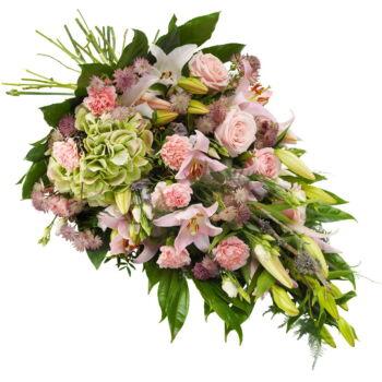 """Indrukwekkend rouwboeket in zachtroze tinten. Dit bevat doorgaans bloemen zoals lelies, anjers, rozen, eustoma, astrantia en seizoensgroen. De afbeelding toont de """"grote"""" variant. Een rouwlint kan eventueel los worden bijbesteld."""