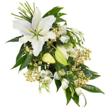 Een prachtig rouwboeket gemaakt van de mooiste witte bloemen, afgewerkt met decoratief seizoensgroen. Bevat onder andere Lelies en eustoma.