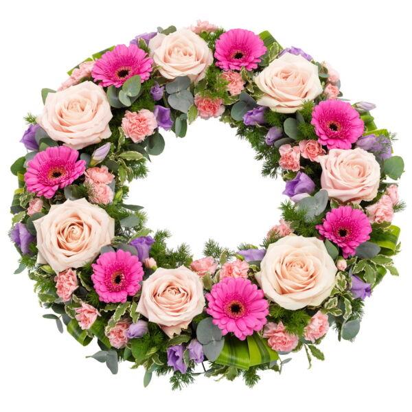 Neem afscheid met deze sierlijke rouwkrans. De krans bevat doorgaans bloemen zoals rozen, mini-gerbera's, lisianthus, trosanjers en seizoensbladgroen.