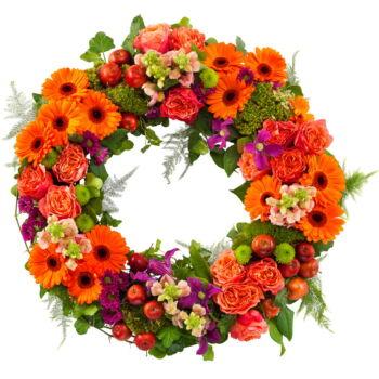 Deze rouwkrans is een klein lichtpuntje in een verdrietige periode. De krans is gedecoreerd met gebera's, rozen, santini en seizoensbloemen afgewerkt met groenblad.